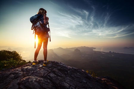 cliff edges: Lady hiker relaxing on top of hill and enjoying sunrise over the valley