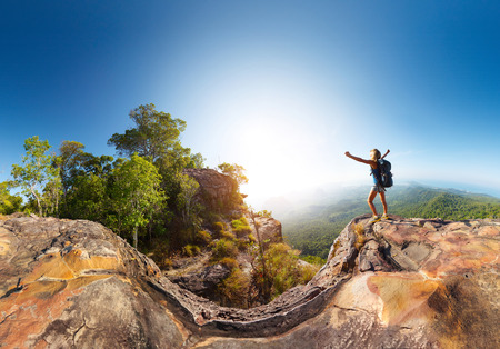Hiker standing on top of the mountain with raised hand photo