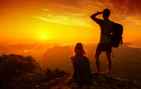 Silhouette of hikers standing on top of hill and enjoying sunrise over the valley