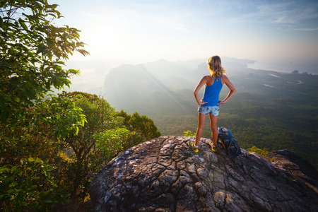 over the hill: Lady hiker relaxing on top of hill and enjoying sunrise over the valley