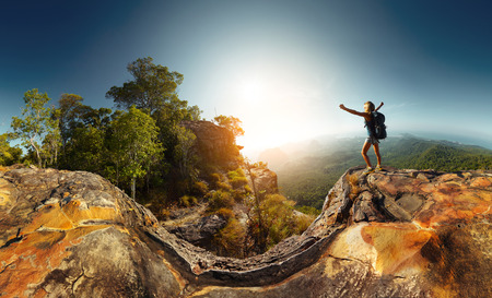 Hiker standing on top of the mountain with raised hand 版權商用圖片 - 31322910