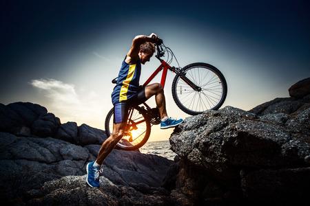 deporte: Jinete de la bicicleta cruzando terreno rocoso al atardecer Foto de archivo