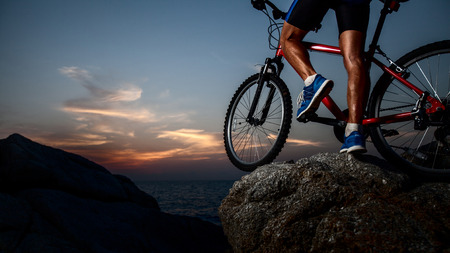 Athlete standing on the rock with bicycle photo