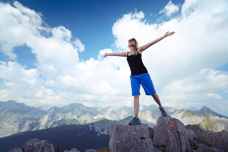 achievment: Young lady standing on top of the hill with raised hands