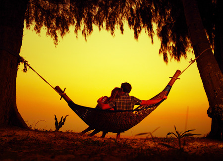 Couple relaxing in a hammock on the trooical beach photo