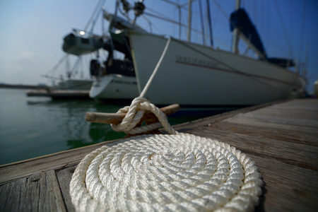 cleat: Coil of the rope on the wooden pier tied up to the yacht. Focus on the coil. Stock Photo