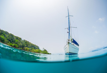 anchored: Split shot of anchored sail boat near green island and clear underwater Stock Photo