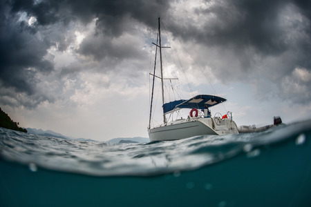 Split shot of anchored sail boat with heavy clouds in sky Archivio Fotografico