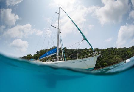 mooring: Split shot of the sail boat anchored near the green island at sunny day
