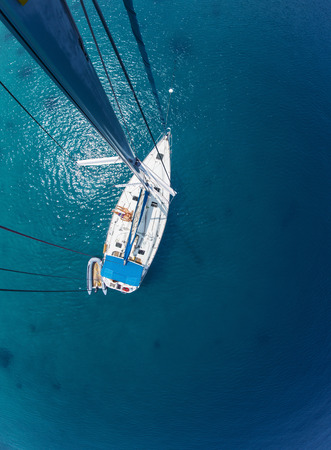 cenital: Pareja joven de relax a bordo del barco de vela anclados en bah�a tropical baja