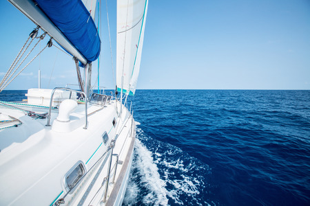 Sail boat with set up sails gliding in open sea at sunny day