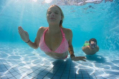 Young couple gliding underwater in the swimming pool Stock Photo