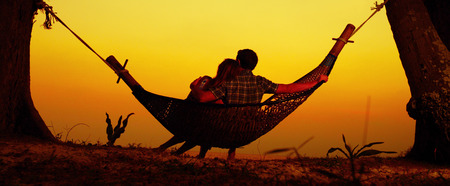 Couple relaxing in the hammock on a trooical beach photo