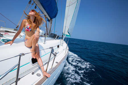 Young lady relaxing on the deck of the sail boat in the tropical sea at sunny day