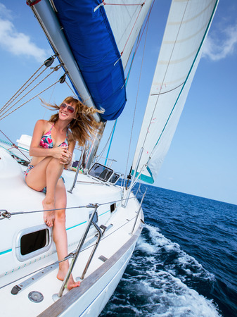 tilt: Young happy lady relaxing on the sail boat in the tropical sea at sunny day