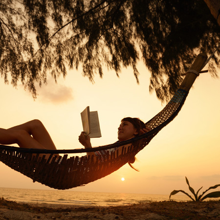 Lady relaxing in the hammock with book Stockfoto