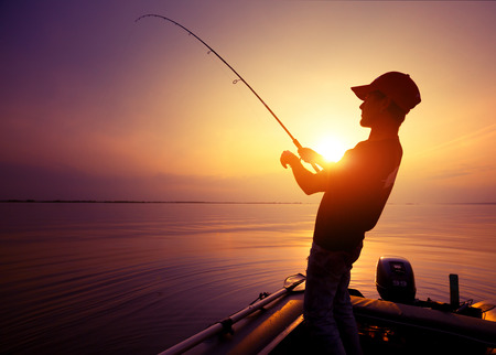 freshwater: Young man fishing on wide river from the boat at sunset