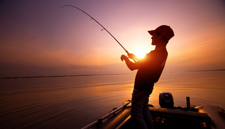 Young man fishing on wide river from the boat at sunset