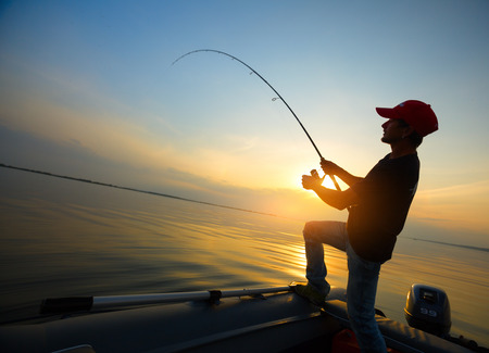 man fishing: Young man fishing on wide river from the boat at sunset