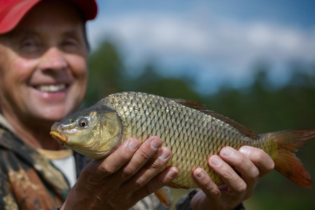 cyprinidae: Happy mature fisherman holding his trophy carp (Cyprinus carpio). Focus on the fish