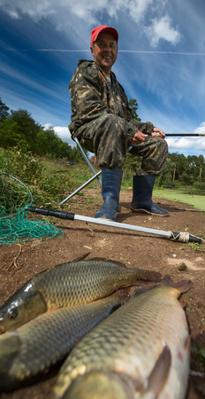 Mature fisherman smiling and looking to his fish (Cyprinus carpio) on the ground photo