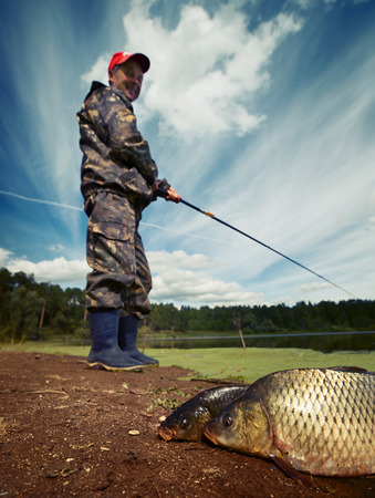 Mature fisherman smiling and looking to his fish (Cyprinus carpio) on the ground. Focus on the fish photo