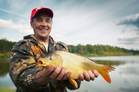 cyprinidae: Happy smiling fisherman holding his trophy carp (Cyprinus carpio)