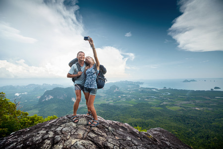 Couple of hikers taking photo of themselves on top of the mountain with green valley  photo