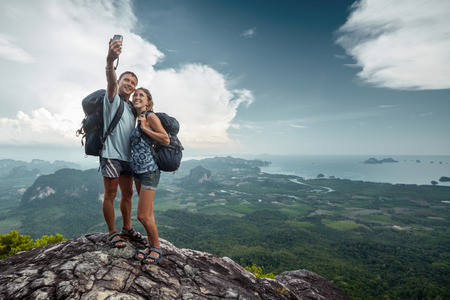 Two hikers taking selfie on top of the mountain photo