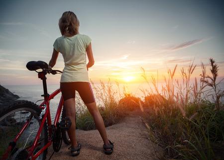 Dame met de fiets naar de zonsondergang