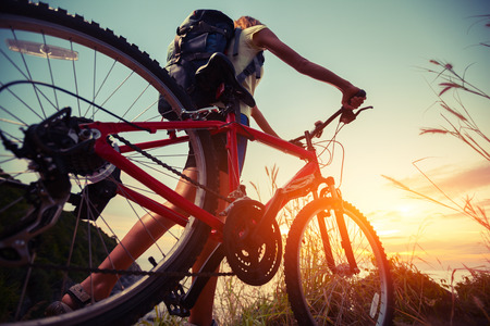mountain bicycle: Hiker with bicycle watching sunset