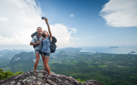 Couple of hikers taking photo of themselves on top of the mountain with green valley