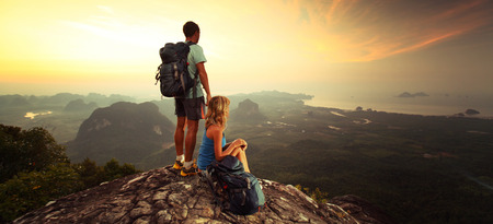 backpack: Young hikers enjoying sunrise on top of the mountain after trekking Stock Photo