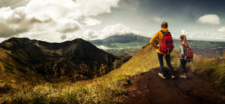 Two ladies with backpacks standing on top of the mountain and enjoying valley view