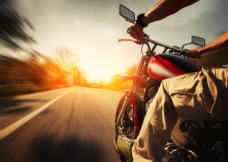 Biker riding motorcycle  on an empty road at sunny day photo