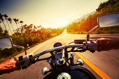 Driver riding motorcycle on an empty asphalt road Stock Photo
