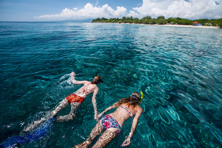 Two ladies snorkeling in the clear tropical sea near the island of Gili Trawangan, Indonesia photo