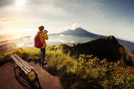 관점에서 산들과 계곡의 사진을 찍는 등산객 사진 작가