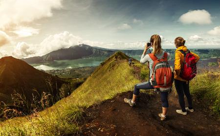 渓谷の景色を楽しんでいると、写真を撮る山の頂上に立っているバックパックと 2 つのハイカー