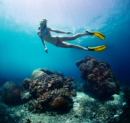 breath hold: Underwater shot of the lady finning over coral reef using a breath hold Stock Photo