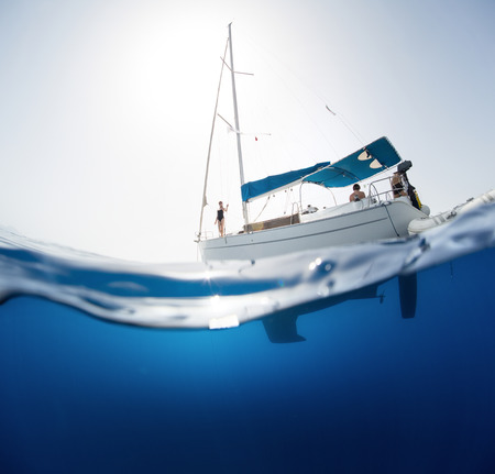 Split shot of the sail boat on surface and its underwater view photo