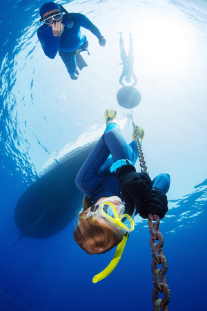 buddy: Lady free diver descending along the metal chain using his hands (free immersion). Safety buddy descending close to athlete