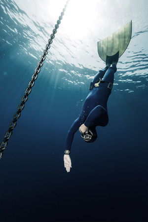 free diver: Underwater shot of free diver in monofin descending along the metal chain
