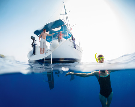keel: Split shot with young lady in swim suit underwater and sail boat on the surface Stock Photo