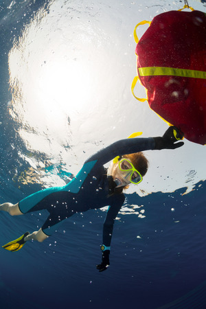 free diver: Young lady free diver relaxing on surface and holding the red buoy