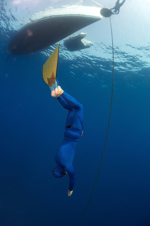 constant: Free diver in monofin descending along the metal chain linked to the boat on surface (constant weight discipline) Stock Photo