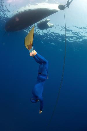 chainlinked: Gratis duiker in monovin aflopend langs de metalen ketting verbonden met de boot op het oppervlak (constant gewicht discipline)