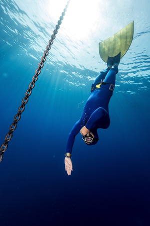 constant: Underwater shot of the free diver in monofin descending along the metal chain. Constant weight discipline
