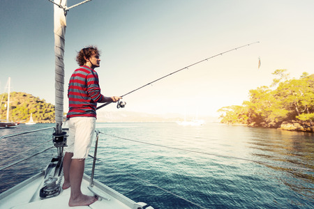 cordage: Young man fishing from the sail boat