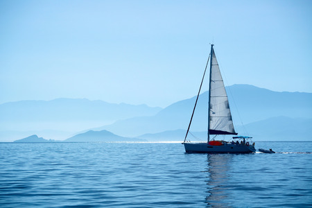 waters: Sail boat crossing calm waters of Skopea Limani gulf, Turkey